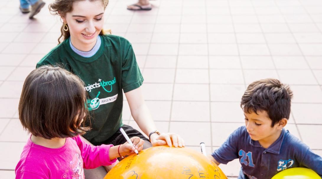 ボールを使って遊ぶアルゼンチンの子供たちとチャイルドケアボランティア